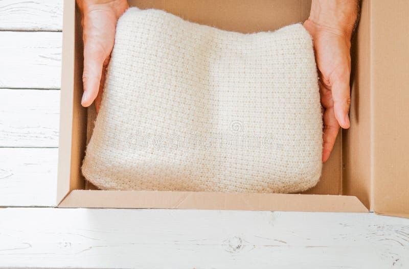 Les mains humaines éteint le nouveau juste arrivé avec le chandail de courrier sur la table en bois blanche image libre de droits