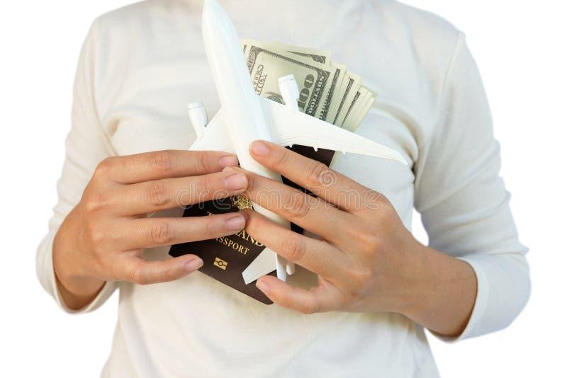 Les mains jugent un passeport et un modèle plat d'isolement sur le fond blanc, pour le concept de planification de voyage image stock