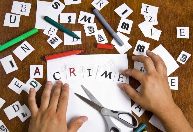 Les mains mâles ont remonté des lettres dans le mot - crime. photographie stock