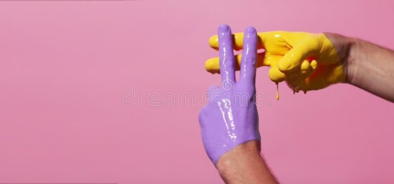 Les mains masculines en peinture ont croisé dans un hashtag pour se connecter un fond coloré, la publicité créative, concept soci photos libres de droits