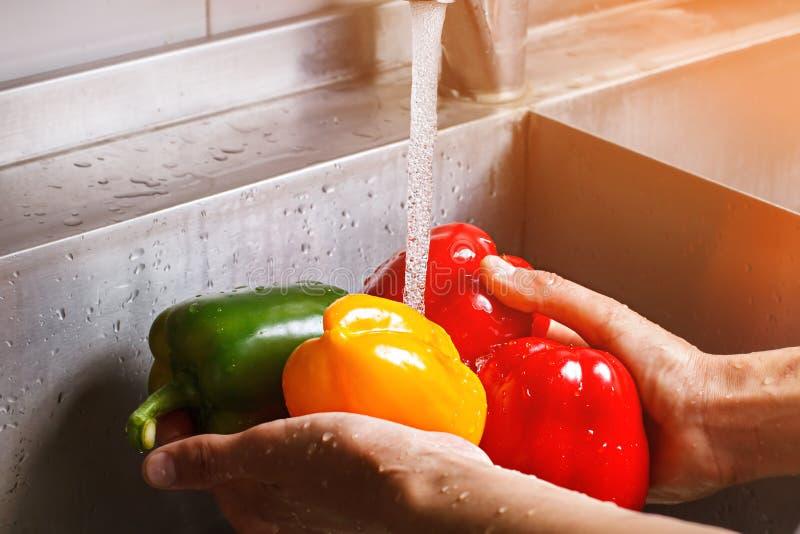Les mains masculines lavent le paprika jaune photos libres de droits