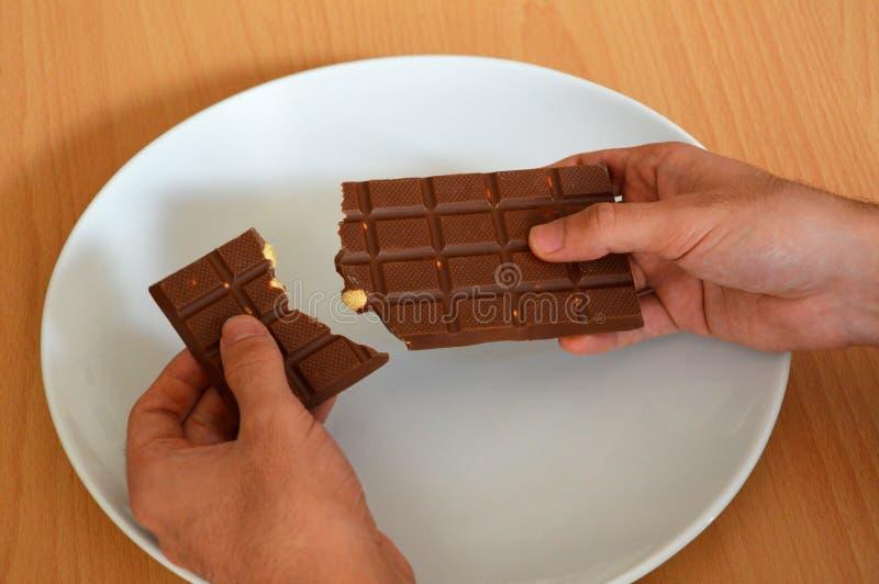 Les mains masculines ont fendu la barre de chocolat d'un plat image stock