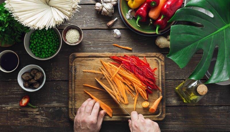 Les mains masculines préparent la cuisine thaïlandaise végétarienne de maison de table de nouilles à photographie stock libre de droits
