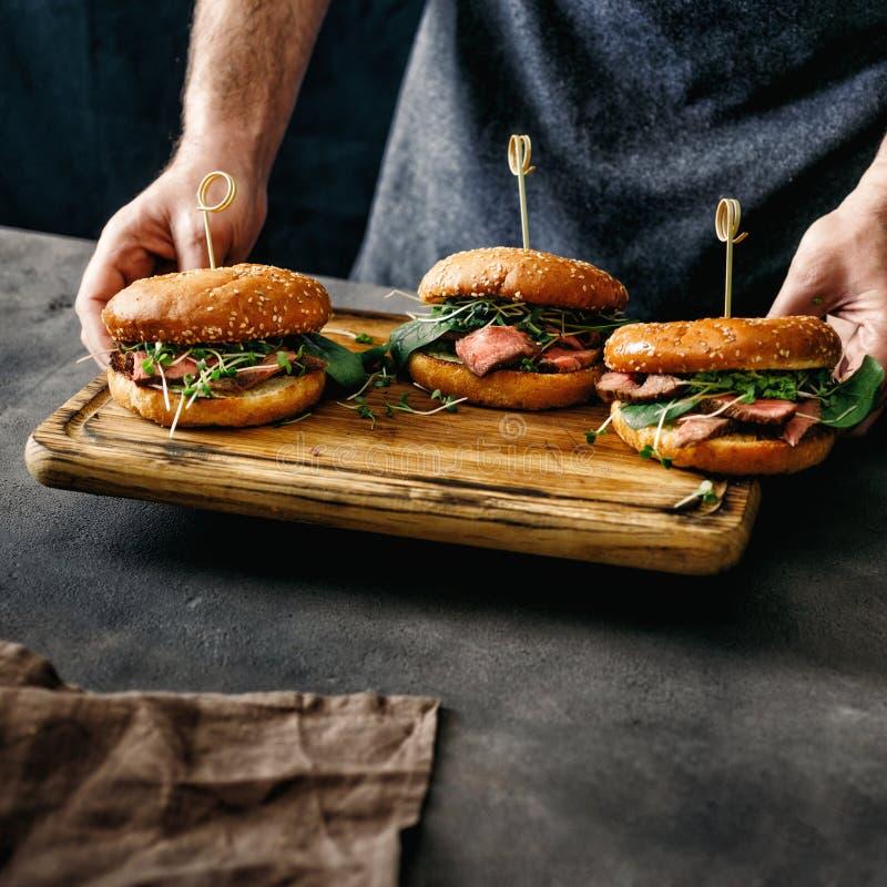 Les mains masculines tenant trois hamburgers ont grillé le backgrou d'obscurité de viande de boeuf photographie stock libre de droits
