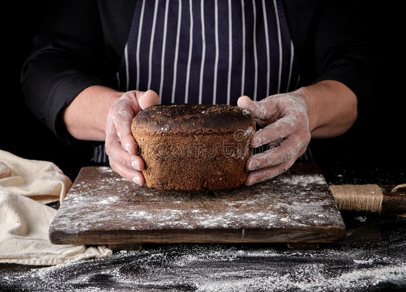 les mains masculines tiennent le pain de seigle cuit au four brun au-dessus du conseil en bois avec de la farine photos libres de droits