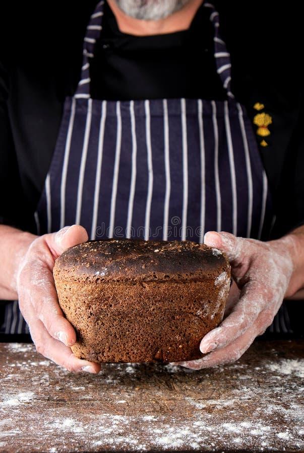 les mains masculines tiennent le pain de seigle cuit au four brun image libre de droits