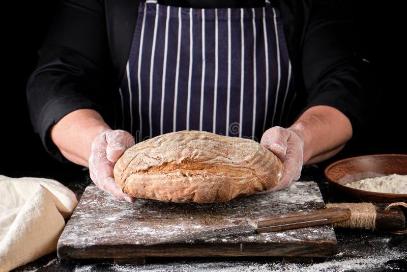 les mains masculines tiennent le pain de seigle cuit au four brun image stock
