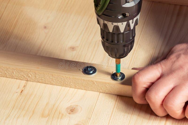 Les mains masculines vissent les blocs en bois aux conseils avec un tournevis image stock