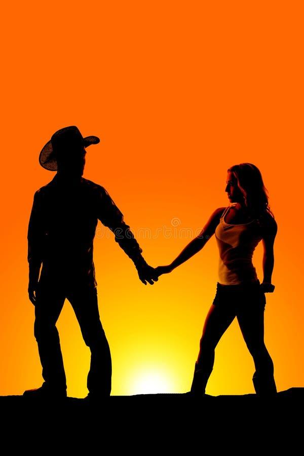 Les mains occidentales de couples de silhouette regardent en arrière photographie stock libre de droits