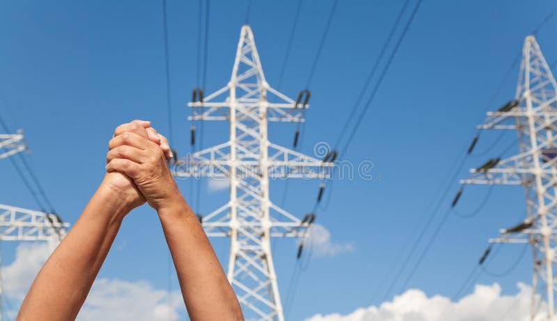 Les mains ont croisé dans des lignes de transport de consentement et d'énergie contre bleu photos libres de droits