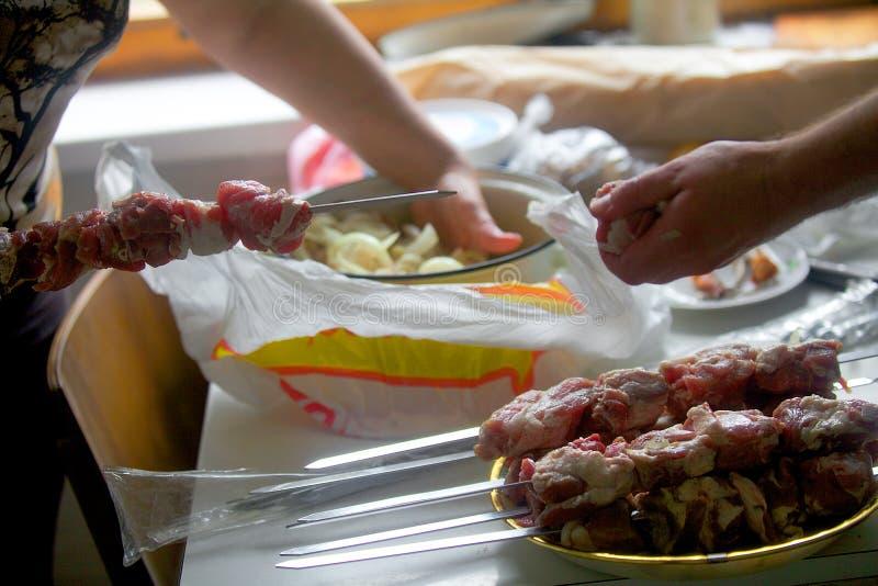 Les mains ont ficelé le morceau de viande sur la brochette Est tout près plein photos libres de droits
