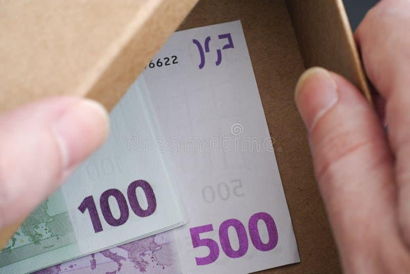 Les mains ouvrent la boîte avec d'euro billets de banque dans elle images libres de droits