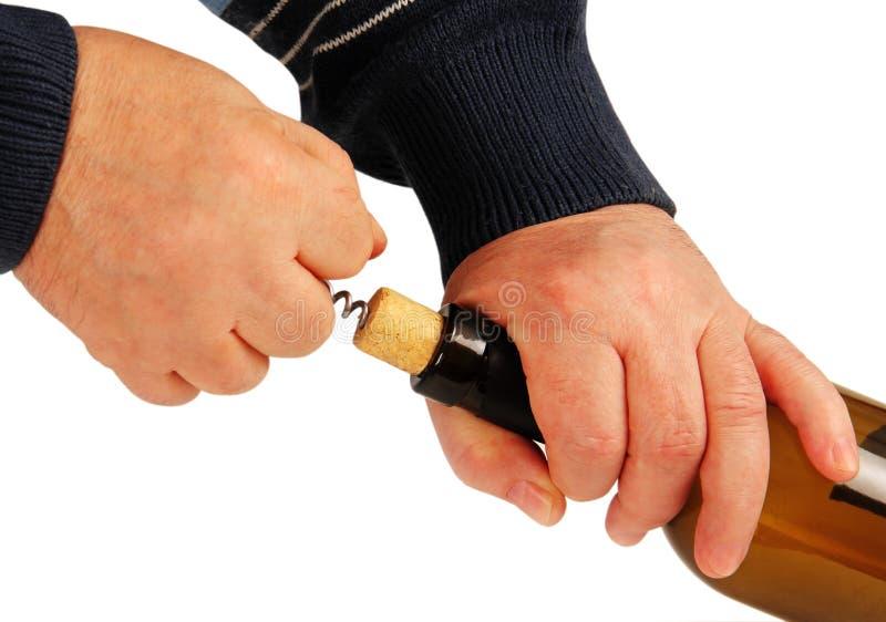 Les mains ouvrent la bouteille de vin. images stock