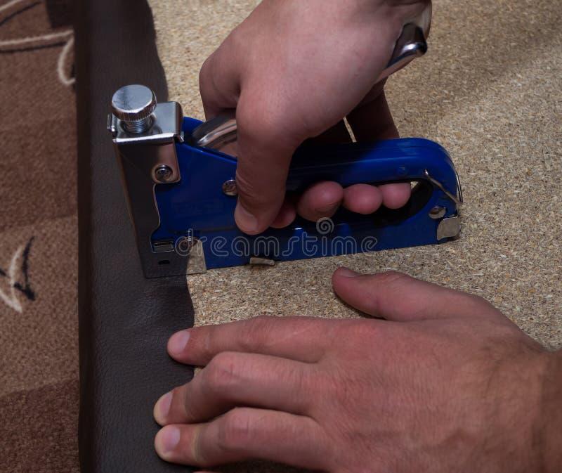 Les mains pour deux hommes utilisant le paricle de tapissage d'agrafeuse embarquent avec le similicuir photo stock