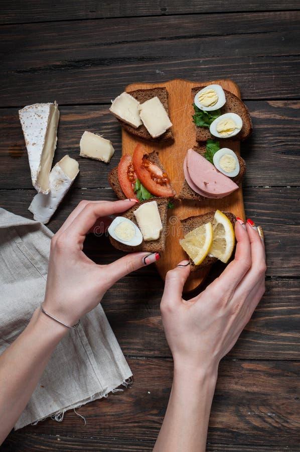 Les mains prend le sandwich avec l'oeuf, les oeufs de caille, les tomates et le fromage image libre de droits