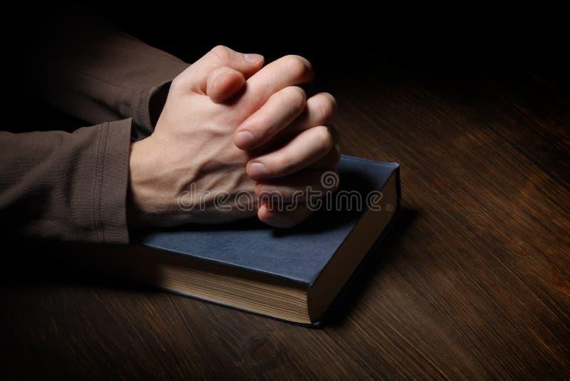 Les mains se sont pliées dans la prière au-dessus d'une bible sainte images stock