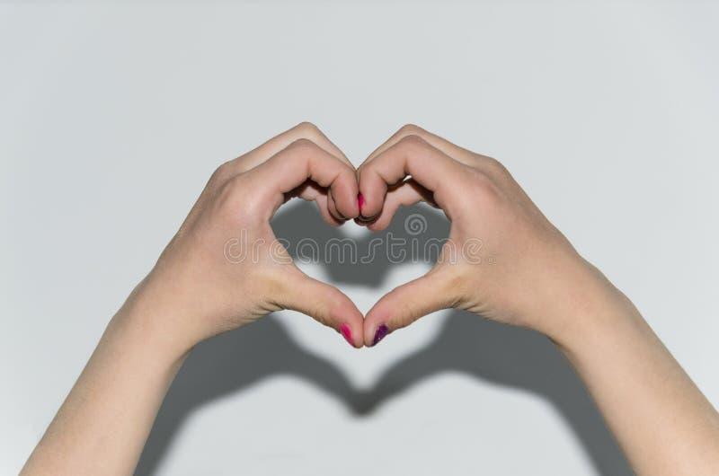 Les mains se sont pli?es sous forme de coeur contre un mur blanc, coeurs d'isolat, les mains des enfants, enfant d'amour image libre de droits