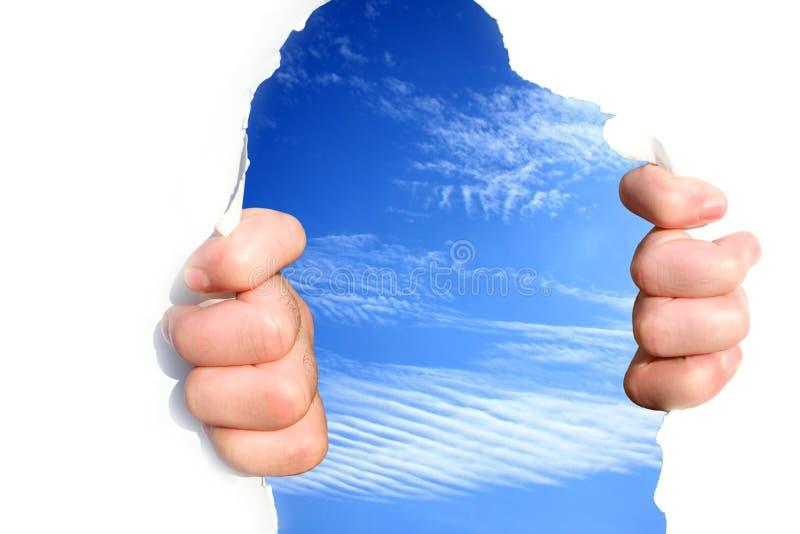 Les mains sur le ciel déchirent un trou photo libre de droits