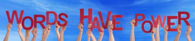 Les mains tenant des mots rouges de Word ont le ciel bleu de puissance photo libre de droits