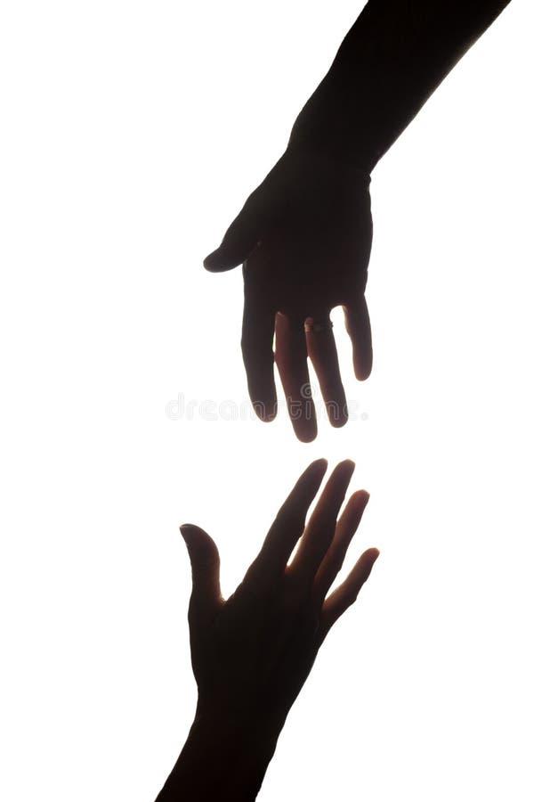 Les mains tendues des femmes et des hommes, délivrance, aide - silhouette images stock