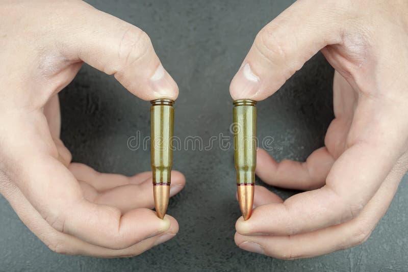 Les mains tiennent deux 7 cartouches de 62 millimètres pour un fusil d'assaut de kalachnikov entre les doigts photos libres de droits