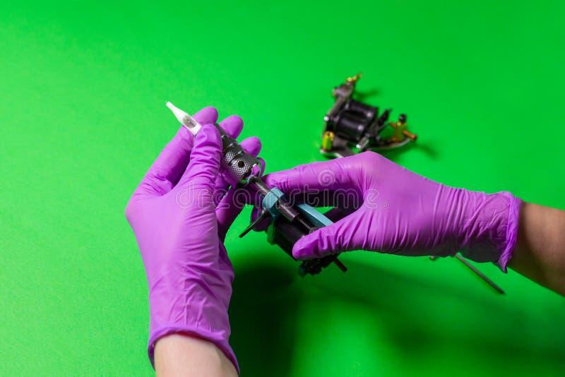 Les mains tiennent une machine bleue de tatouage photos libres de droits