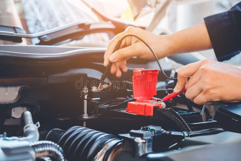 Les mains vérifient le mécanicien de voiture de batterie travaillant dans le service des réparations automatique photo libre de droits