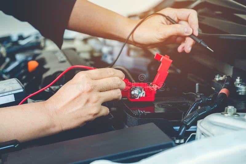 Les mains vérifient le mécanicien de voiture de batterie travaillant dans le service des réparations automatique image libre de droits