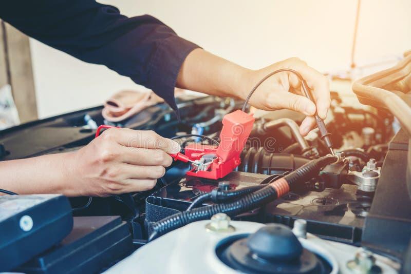 Les mains vérifient le mécanicien de voiture de batterie travaillant dans le service des réparations automatique images libres de droits