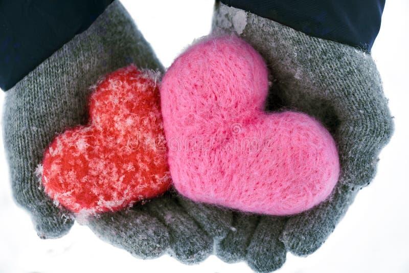 Les mains wollen dedans des gants jugeant deux coeurs de laine couverts de flocons de neige d'isolement photographie stock libre de droits