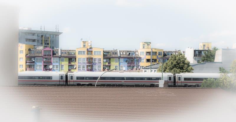 Les maisons colorées affrontent avec déplacer le train interurbain à Berlin images stock