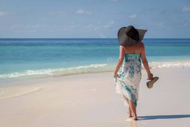 Les Maldives, jeune femme marchant le long de la plage avec le chapeau de soleil et des talons hauts sur la main photo libre de droits