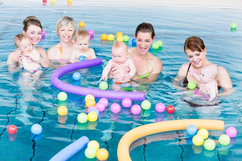 Les mamans et les bébés jouant à la natation infantile classent photos stock