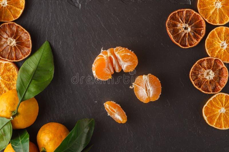 Les mandarines avec des feuilles et sèchent l'orange coupée en tranches au-dessus de l'ardoise noire su photographie stock