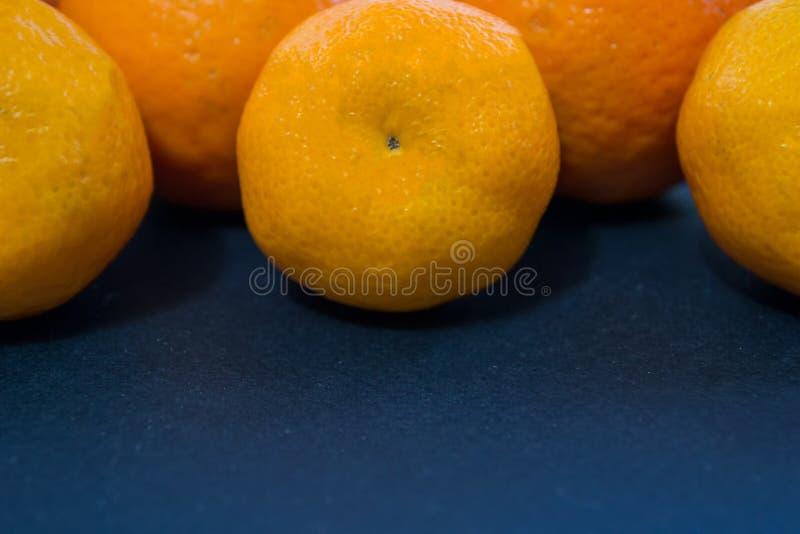 Les mandarines lumineuses se trouvent harmonieusement sur un fond bleu-foncé photographie stock libre de droits