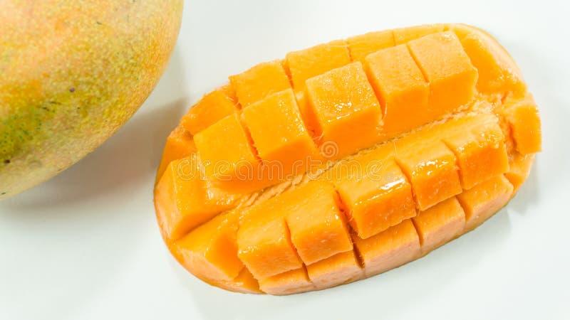 Les mangues mûres à l'arrière-plan blanc/ont coupé en tranches la mangue délicieuse pour manger image stock