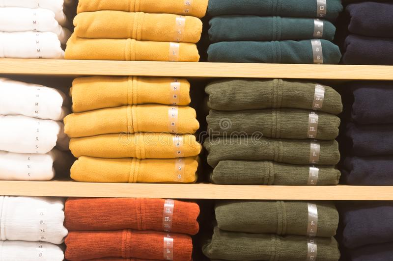 Les manteaux colorés d'hiver se sont pliés et planton empilé sur une étagère images stock