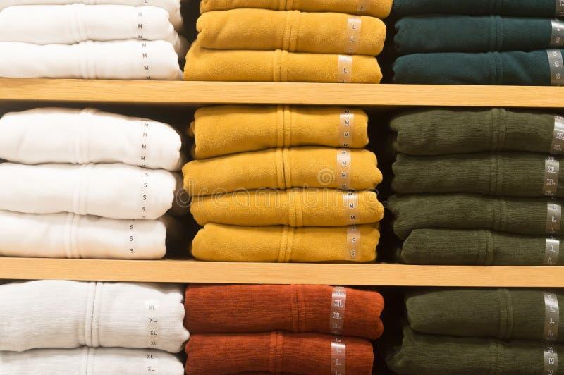 Les manteaux colorés d'hiver se sont pliés et planton empilé sur une étagère photographie stock