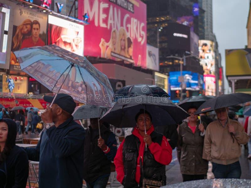 Les marcheurs tiennent des parapluies regardant les enseignes au néon du Times Square dessus photographie stock libre de droits