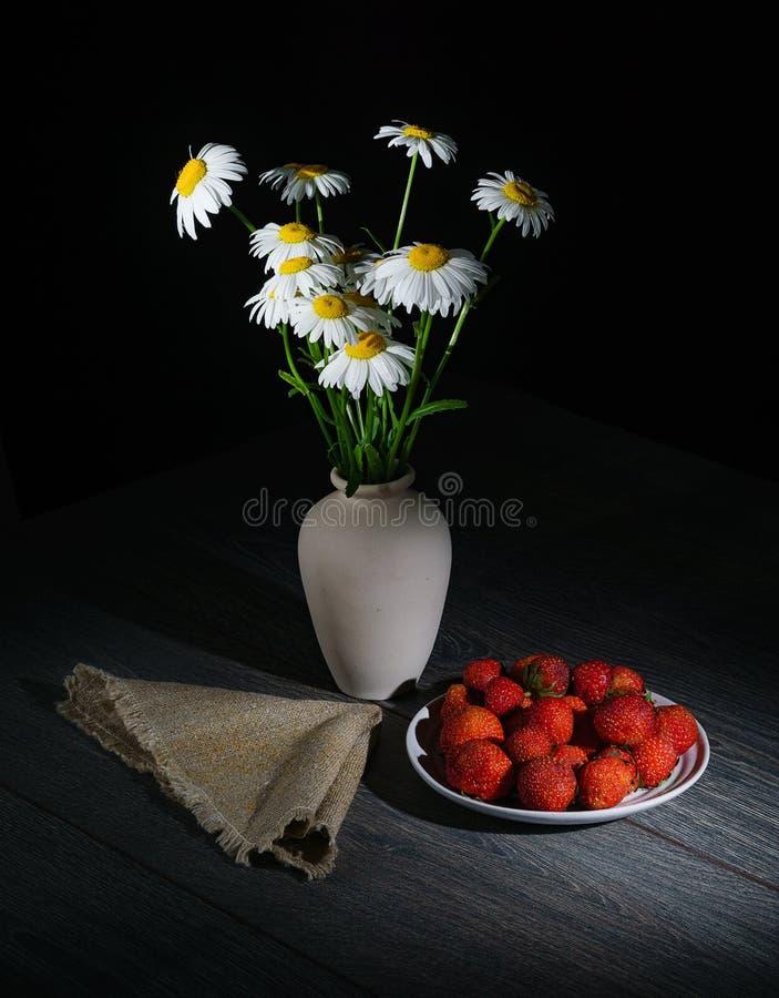 Les marguerites alba, cette camomille blanche dispose à dormir, à côté d'une serviette et d'un plat des fraises fraîches photographie stock libre de droits