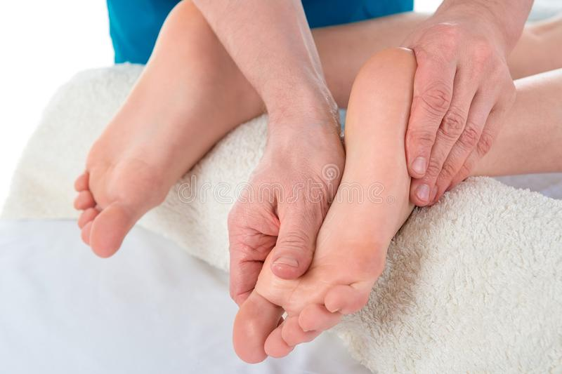 Les massages manuels masculins d'un thérapeute professionnel de massage et épuise les jambes et les pieds de la patiente de femme images libres de droits