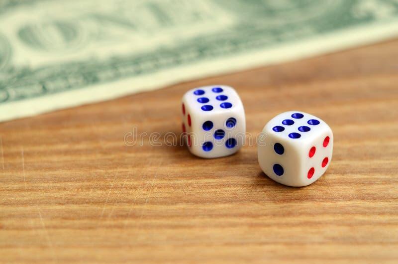 Les matrices blanches sont à côté d'un billet d'un dollar des dollars US sur un fond en bois Le concept du jeu avec des taux dans photographie stock