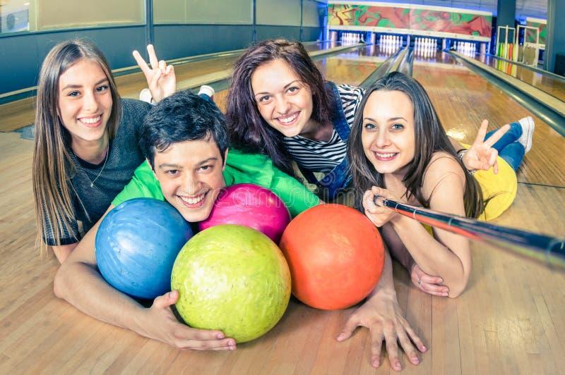 Les meilleurs amis employant le selfie collent prendre la PIC sur la voie de bowling images libres de droits
