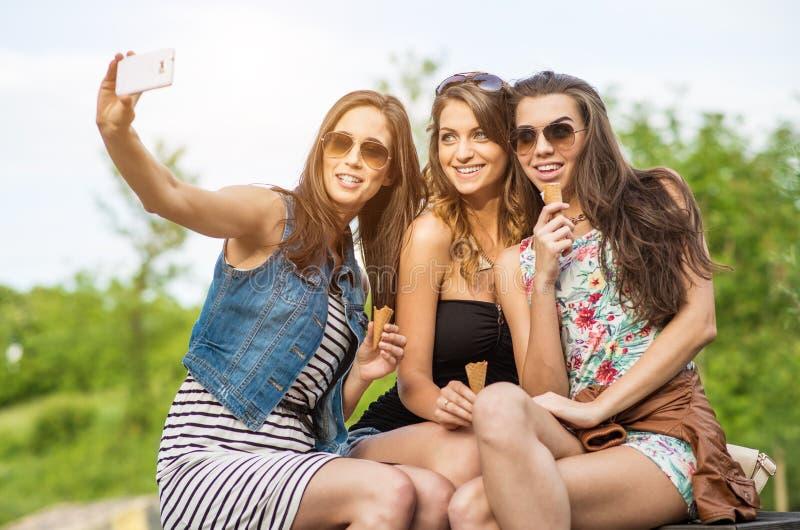 Les meilleurs amis Selfie - belle femme trois mangeant la crème glacée  image stock