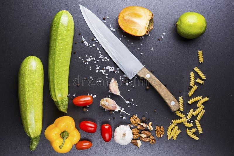 Les meilleurs ingrédients sont le chef du ` s de chef Sur les légumes, le couteau et les épices en céramique noirs de table pour  photo stock