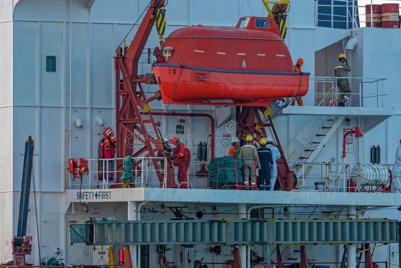 Les membres d'équipage du navire de charge en vrac ancré effectue leur travail sur la plate-forme de bateau photographie stock libre de droits