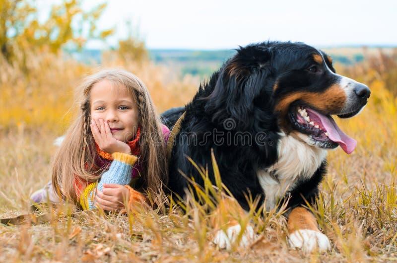 les mensonges de fille à côté du grand chien l'automne marchent photographie stock libre de droits