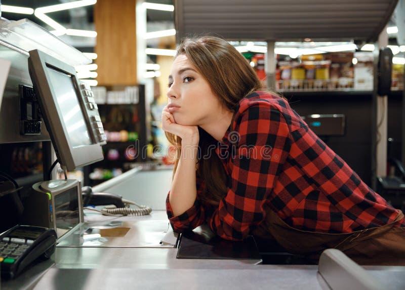Les mensonges fatigués de dame de caissier sur l'espace de travail dans le supermarché font des emplettes photos libres de droits