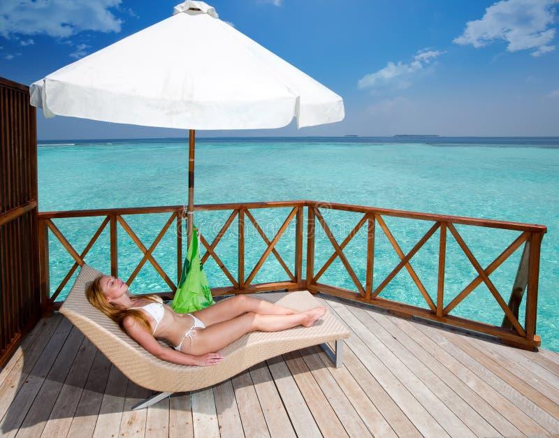 Les mensonges les prenant un bain de soleil de blonde sur un salon de cabriolet contre l'océan tropical photo stock