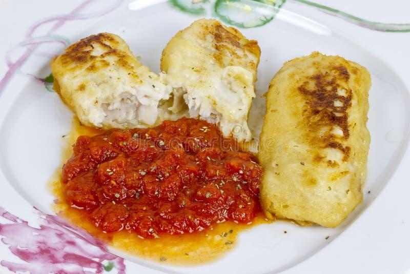 Les merluches ceignent d'un bandeau avec la sauce tomate fraîche photos stock